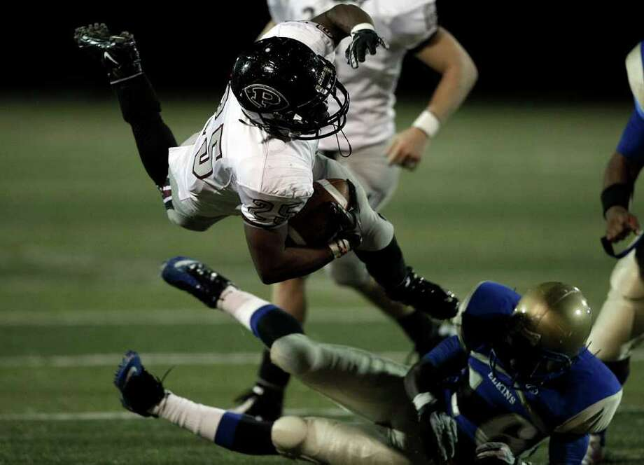 Pearland running back Jackie Robinson #25 leaps over Elkins' Michael Matthews #56 during a first round playoff game between the Pearland Oilers and Elkins Knights Friday, November 11, 2011 in Alvin, Texas, Photo: Bob Levey, Houston Chronicle / ©2011 Bob Levey