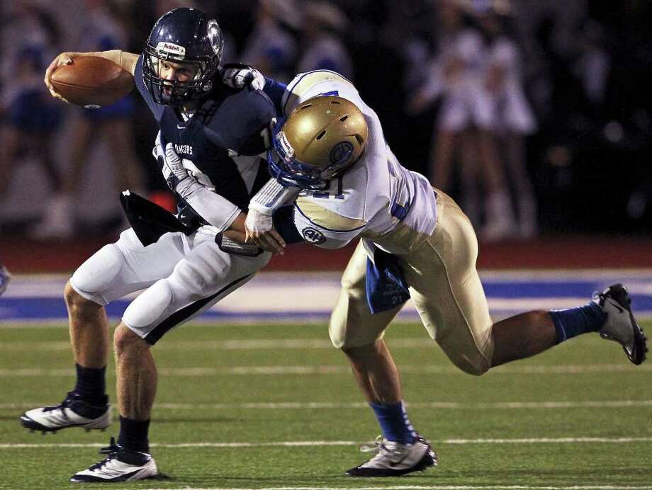 Champion quarteback Kyle Poeske is tackled by Nick Uretsky in the first half as Alamo Heights plays Boerne Champion at New Braunfels High School Stadium in the first round of playoff action on November 11, 2011. Photo: TOM REEL, Express-News / © 2011 San Antonio Express-News