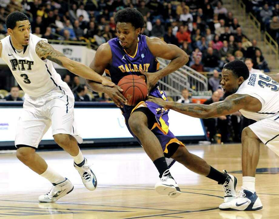 Albany guard Gerardo Suero drives the ball as Pittsburgh guard Cameron Wright (3) and Nasir Robinson (35) defend during the first half of an NCAA college basketball game Friday, Nov. 11, 2011, in Pittsburgh. (AP Photo/Don Wright) Photo: Don Wright