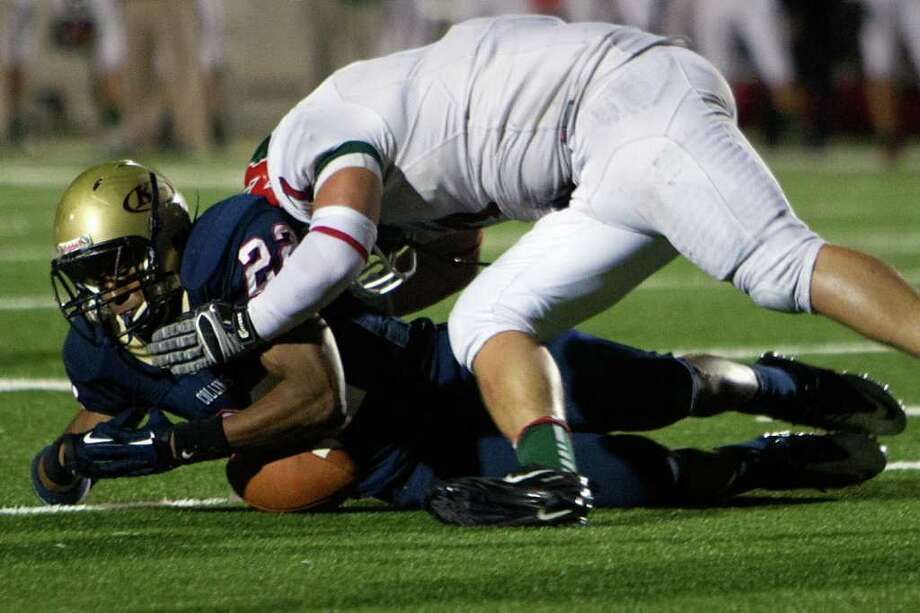 Klein Collins running back Ellison Powell (22) fumbles as he is hit by The Woodlands linebacker Robbie Goldschmidt (7) during the fourth quarter of a high school football playoff game at Turner Stadium, Friday, Nov. 11, 2011, in Humble. The Woodlands won the game 42-31. Photo: Smiley N. Pool, Houston Chronicle / © 2011  Houston Chronicle