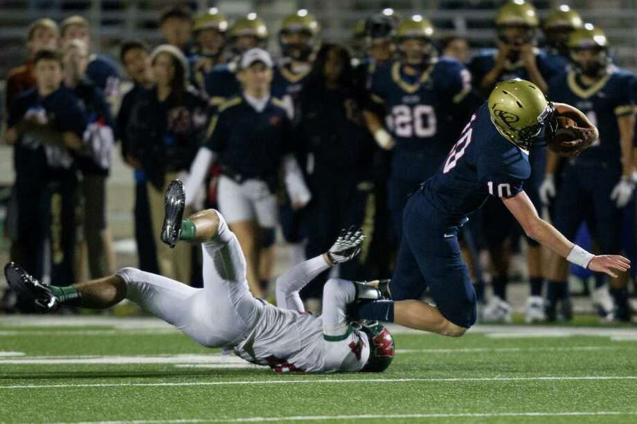Klein Collins quarterback Tyler Stehling (10) is tripped up by The Woodlands defender Christian Jauregui (4) during the third quarter of a high school football playoff game at Turner Stadium, Friday, Nov. 11, 2011, in Humble. Photo: Smiley N. Pool, Houston Chronicle / © 2011  Houston Chronicle