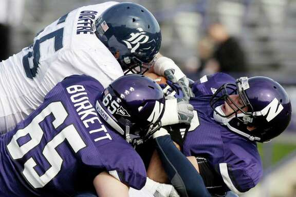 Northwestern tight end Drake Dunsmore, right, is tackled by Rice nose tackle John Gioffre (55) in the first half of an NCAA college football game, Saturday, Nov. 12, 2011, in Evanston, Ill. (AP Photo/Nam Y. Huh)