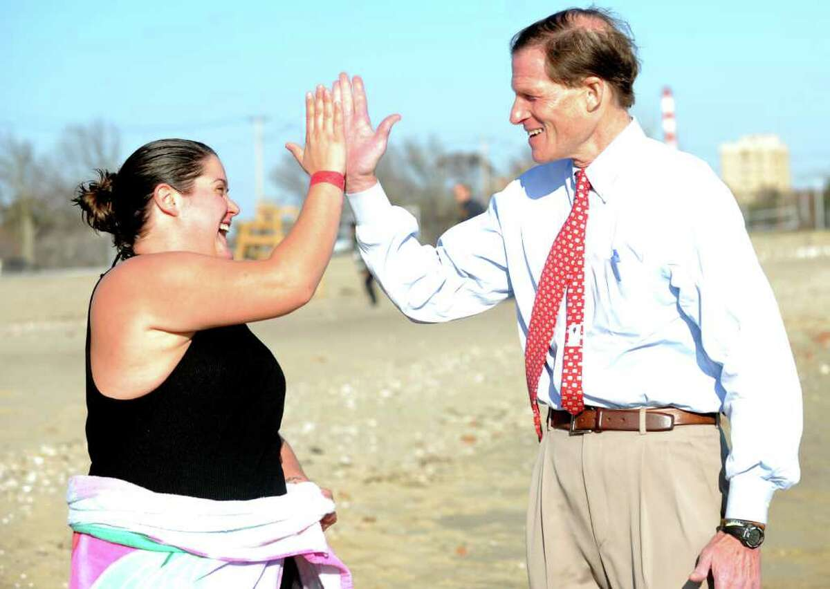 Angelina Nuccio, of Seymour, gets a high five from Sen. Richard Blumenthal after plunging into the Long Island Sound during the first Seaside Park Splash and Stroll presented by Bridgeport law enforcement to benefit Special Olympics Saturday, Nov. 12, 2011 at Seaside Park in Bridgeport, Conn.