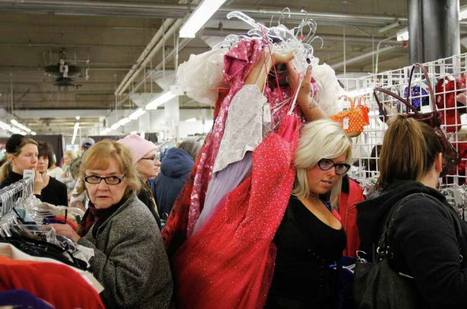 Hundreds of bargain hunters awoke early  on Saturday Nov. 12, 2011 for Seattle Goodwill's annual Glitter Sale of glitzy and glamorous clothing, jewelry, and bags. Maya Cichon, shown here making her way through the crowd of shoppers, lined up outside the Dearborn Street store at 5:30 a.m. to be part of the first batch of shoppers allowed in.  All of the proceeds from the sale go to support Goodwill's free job training and educational programs. Photo: JOE DYER / SEATTLEPI.COM