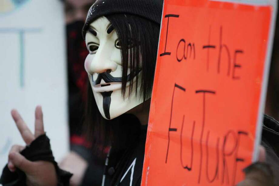 METRO -- An Occupy San Antonio member holds up a sign as they attempt to bring attention to their cause as they gather at HemisFair Plaza, Wednesday, Nov. 9 2011. JERRY LARA/glara@express-news.net Photo: JERRY LARA, San Antonio Express-News / SAN ANTONIO EXPRESS-NEWS