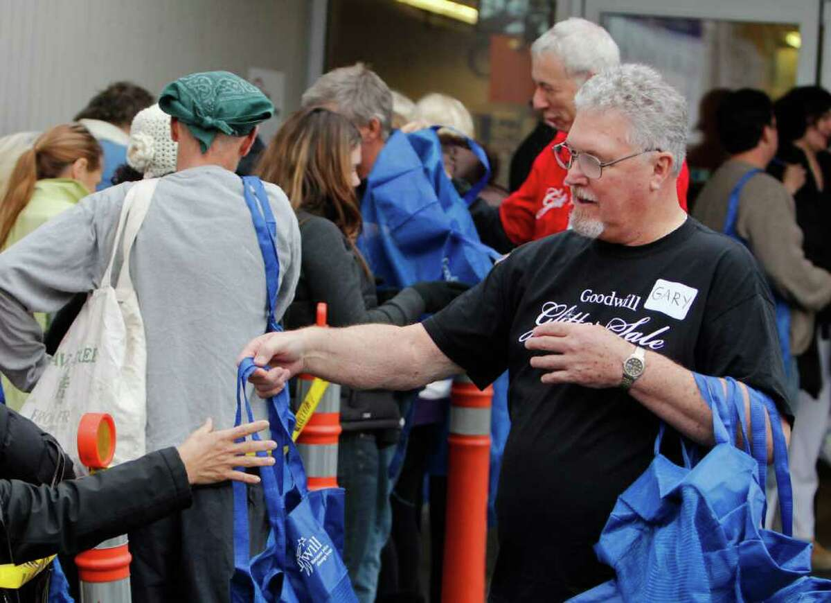 Goodwill employees pass out reuseable bags to shoppers moments before the opening of the Glitter Sale at the Seattle Goodwill's Dearborn Street store on Saturday Nov. 12, 2011. The Glitter Sale is an annual sale featuring glitzy and glamorous clothing, jewelry, and bags. All of the proceeds from the sale go to support Goodwill's free job training and educational programs.