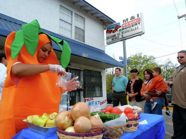 Rosanna Alvarez, left, wears a carrott costume Saturday Nov. 12, 2011 while giving out free produce at M&I Meat Market, as part of a city program to encourage convenience stores to sell healthy food. Photo: JOHN TEDESCO, SAN ANTONIO EXPRESS-NEWS / © 2011 San Antonio Express-News