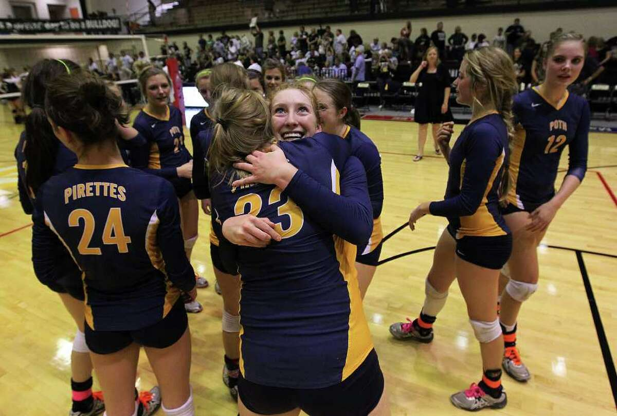 Poth's Avery Acker (facing front) exchanges hugs with teammate Claire Raabe (23) after their team defeated Marion in Region IV-2A volleyball in the championship game at Littleton Gym on Saturday, Nov. 12, 2011. Poth defeated Marion in three straight to move onto the state tournament.