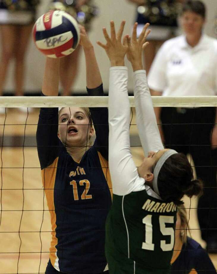 Poth's Jordan Kotara (12) manuevers a shot around Marion's Rachel Farris (15) during the Region IV-2A volleyball championship game at Littleton Gym on Saturday, Nov. 12, 2011. Poth defeated Marion in three straight games to move onto the state tournament. Photo: Kin Man Hui, ~ / San Antonio Express-News