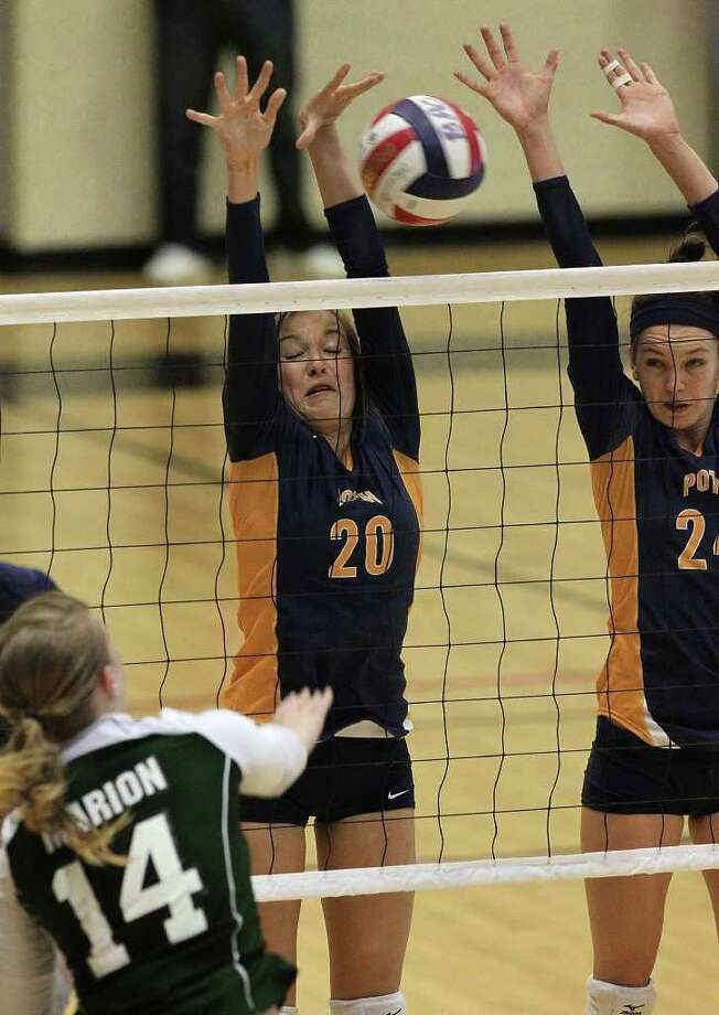 Poth's Tara Broyles (20) and Micah Weaver (24) attempt to block a shot by Marion's Tara Pogue (14) during the Region IV-2A volleyball championship game at Littleton Gym on Saturday, Nov. 12, 2011. Poth defeated Marion in three straight games to move onto the state tournament. Photo: Kin Man Hui, ~ / San Antonio Express-News