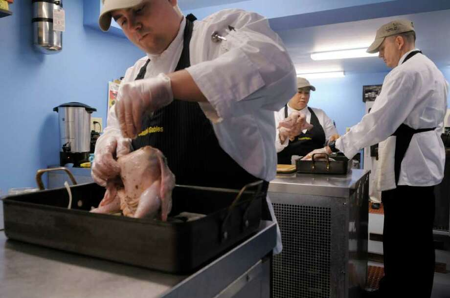 Veterans Michael Hardiman, left, from Reno, NV and Shirley Perez Acosta, background left, from Pisa Italy and Kevin Kett from Tucson, AZ season whole chickens as get the birds ready for roasting at  Bezalel Gables Catering on Thursday, Oct. 27, 2011 in Chatham.  David James Robinson, chef/owner of the catering business is hosting six veterans from around the country as he trains them in a variety of culinary skills to prepare them for the workforce.  (Paul Buckowski / Times Union) Photo: Paul Buckowski / 00015108A