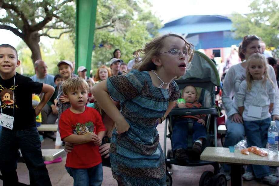 Bailey Reilly, 9, of Pearland, dances like a turkey before a turkey calling contest to promote this year's TXU Energy Turkey Trot benefiting Sheltering Arms Senior Services at the Houston Zoo's McGovern Children's Zoo. Photo: Johnny Hanson, Houston Chronicle / © 2011 Houston Chronicle