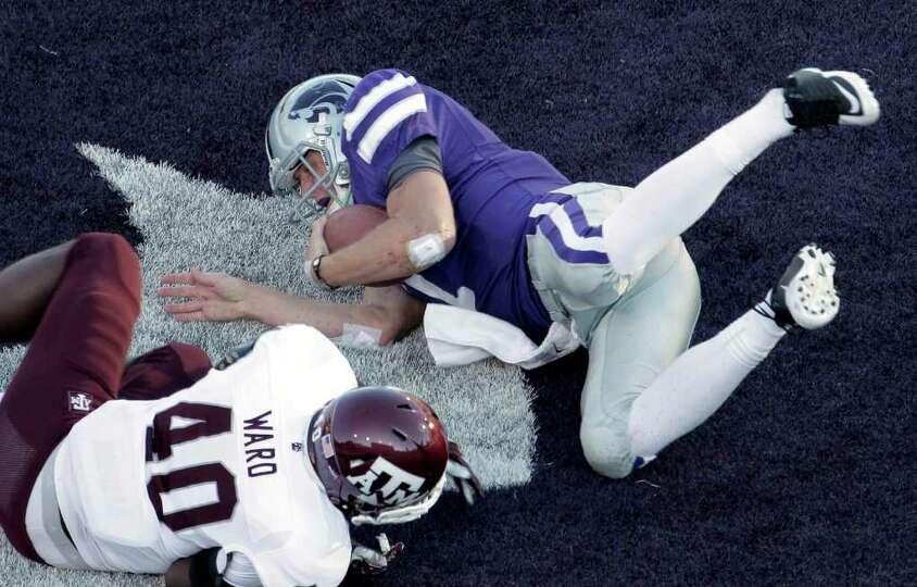 Kansas State quarterback Collin Klein, top, gets past Texas A&M linebacker Shaun Ward (40) to sco