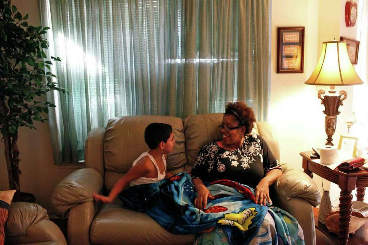 Yvonne Gaines calms her son, David Gaines, 8, who did not want to get ready for bed at their home.