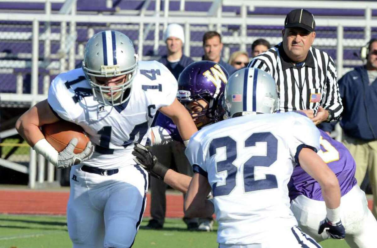 Staples' ball carrier Peter Bonefant (14) avoids a tackle by Westhill's Nick Jimenez (33) during the football game at Westhill High School on Saturday, Nov. 12, 2011.