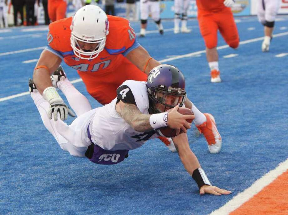 TCU's Casey Pachall (4) rushes for a two point conversion against Boise State's Tyrone Crawford during the second half of an NCAA college football game on Saturday, Nov. 12, 2011 in Boise, Idaho.  TCU went on to upset BSU 36-35.(AP Photo/The Idaho Statesman, Joe Jaszewski)  MANDATORY CREDIT Photo: AP