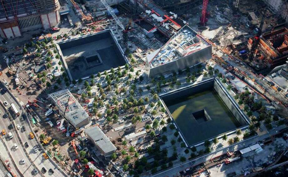 In this aerial photo of July 28, 2011, a grove of trees surround massive square reflecting pools at the National September 11 Memorial in New York. The memorial will open to the public on Sept. 12, 2011.  Out of the ashes of 9/11 has risen a vibrant neighborhood packed with new restaurants and hotels, places to live and spots to shop, along with many ways to pay respects to an area some worried would never come back. A decade after the attack on the World Trade Center, Lower Manhattan draws roughly 9 million of the city's nearly 50 million visitors a year, including the area around ground zero.   (AP Photo/Mark Lennihan) Photo: Mark Lennihan