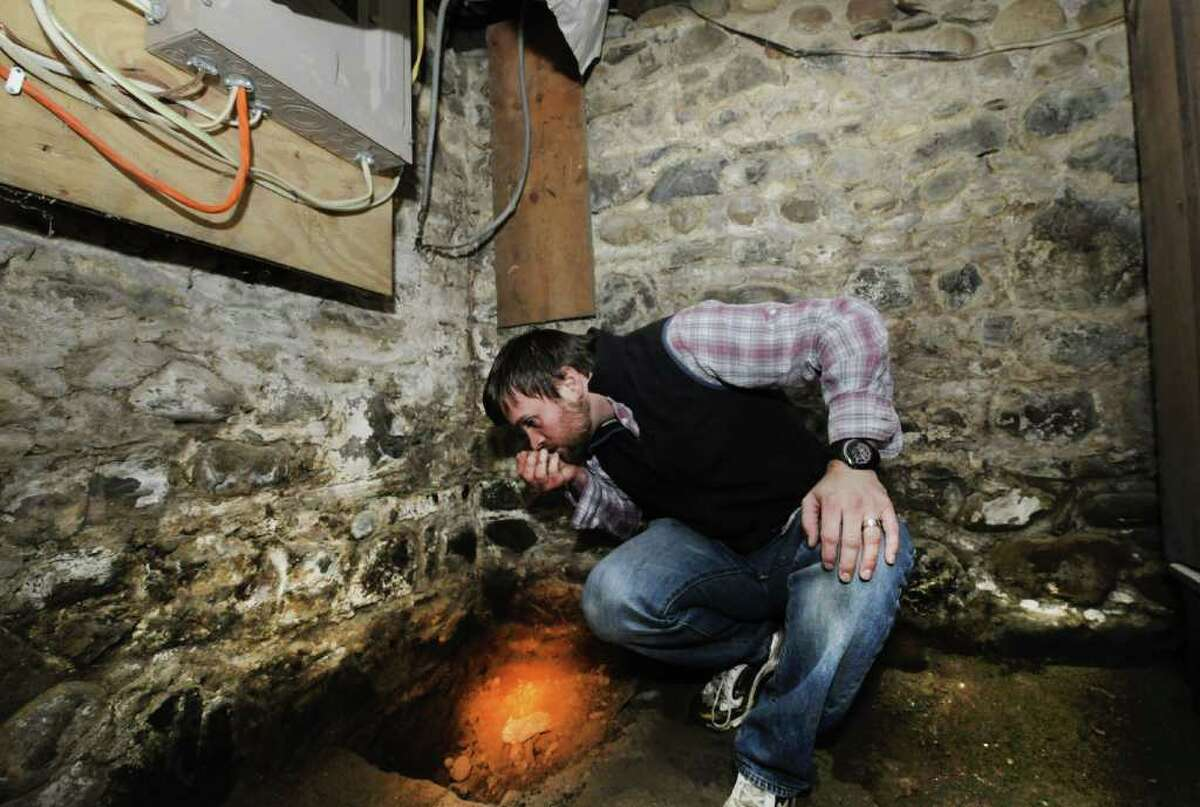 John Young sniffs some of the dirt from beneath the slab floor in the basement of his home in West Sand Lake, N.Y. Young found a distinct odor of heating oil in the dirt. (Skip Dickstein/Times Union)