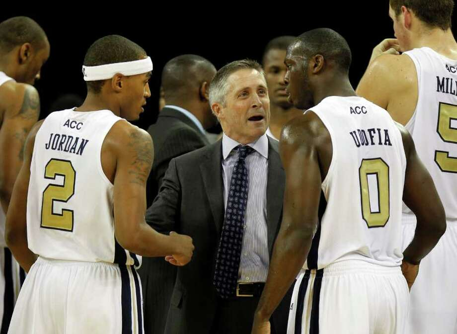 Georgia Tech  head coach Brian Gregory, center, talks with  guard Pierre Jordan (2) and guard Mfon Udofia (0) in the first half of an NCAA college basketball game against the Florida A&M  in Duluth, Ga., Friday, Nov. 11, 2011.  The game was Gregory's first as Tech's head coach. (AP Photo/John Bazemore) Photo: John Bazemore