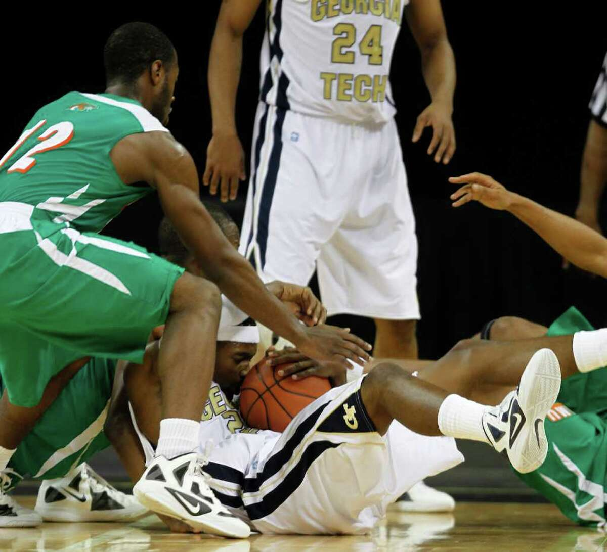 Georgia Tech guard Brandon Reed (23) and Florida A&M forward Reggie Lewis (12), left, scramble for a loose ball in the first half of an NCAA college basketball game in Duluth, Ga., Friday, Nov. 11, 2011. (AP Photo/John Bazemore)