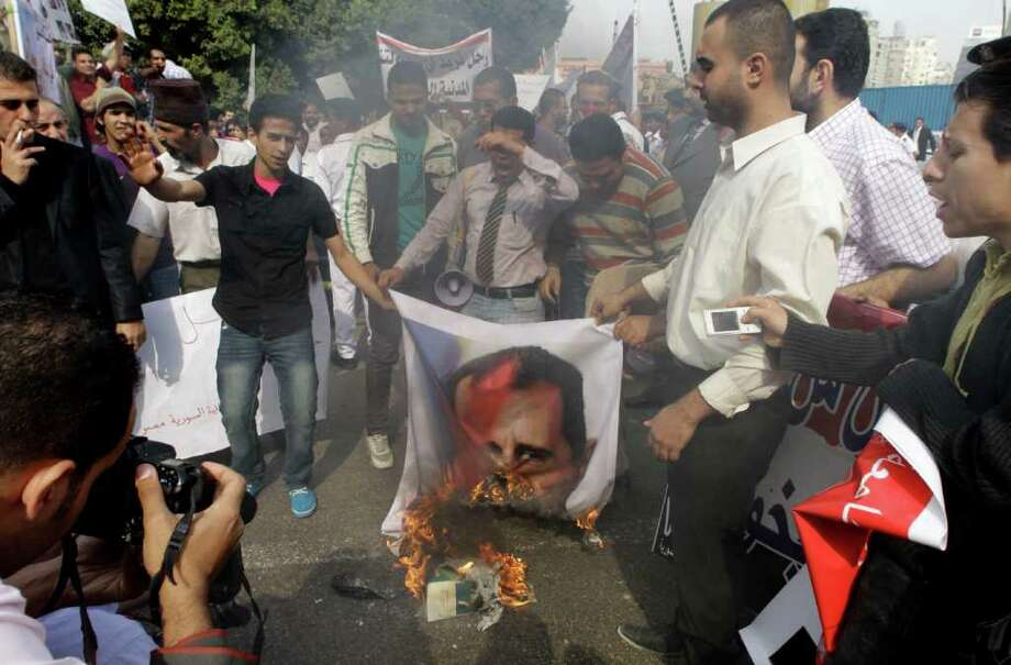 Syrian protesters burn a picture of Syrian President Bashar Assad during a protest in front of the Arab League headquarters in Cairo, Egypt, Saturday, Nov.12, 2011 where an Arab League  emergency session on Syria is to discuss the country's failure to end bloodshed caused by government crackdowns on civil protests. Protesters called on the Arab League to suspend the country's membership. (AP Photo/Amr Nabil) Photo: Amr Nabil / AP