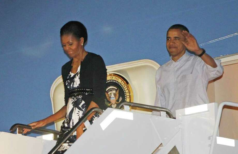 President Barack Obama and first lady Michelle Obama disembark Air Force One as they arrive at Hickam Air Force Base in Honolulu, Hawaii, where they will host the APEC summit, Friday, Nov. 11, 2011.  (AP Photo/Charles Dharapak) Photo: Charles Dharapak