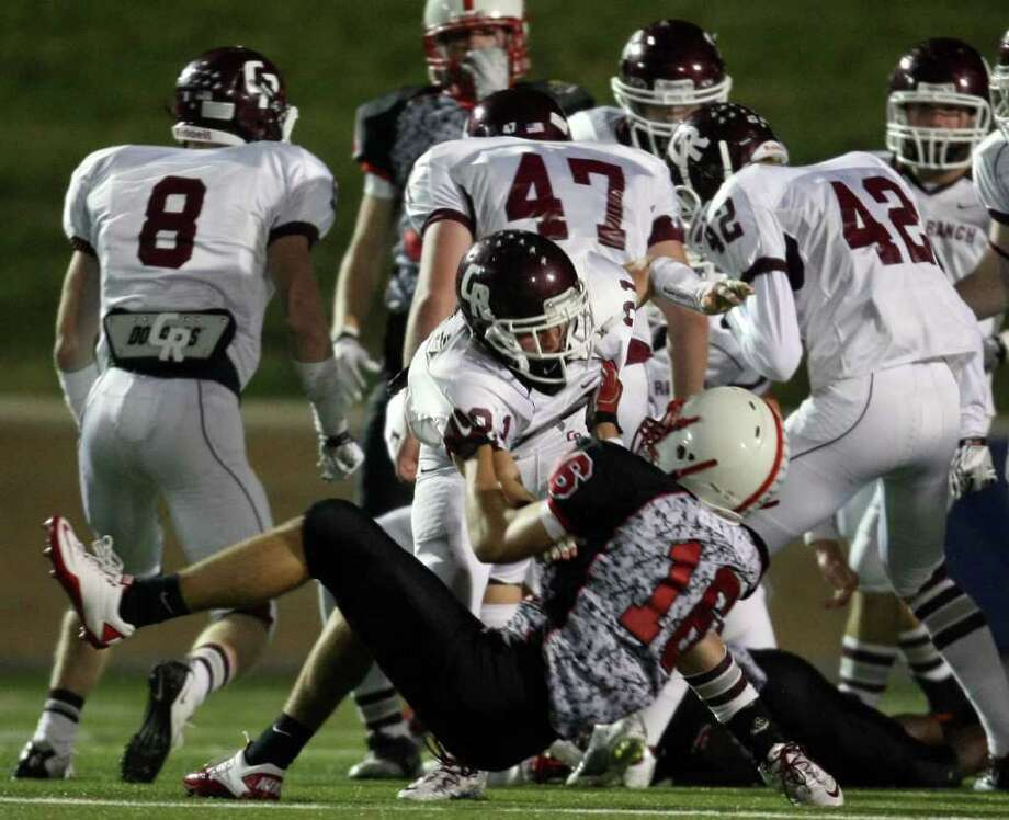 Cinco Ranch's Russell Cuellar (21) and Bellaire's Sam Harker tussle after a play during the first half of a high school football playoff game, Saturday, November 1, 2011 at Tully Stadium in Houston. Photo: Eric Christian Smith, For The Chronicle