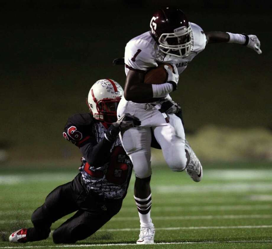 Cinco Ranch's James Rhoden (1) fights for extra yardage after a reception as Bellaire's gabe Byrd tries to make the tackle during the first half of a high school football playoff game, Saturday, November 1, 2011 at Tully Stadium in Houston. Photo: Eric Christian Smith, For The Chronicle