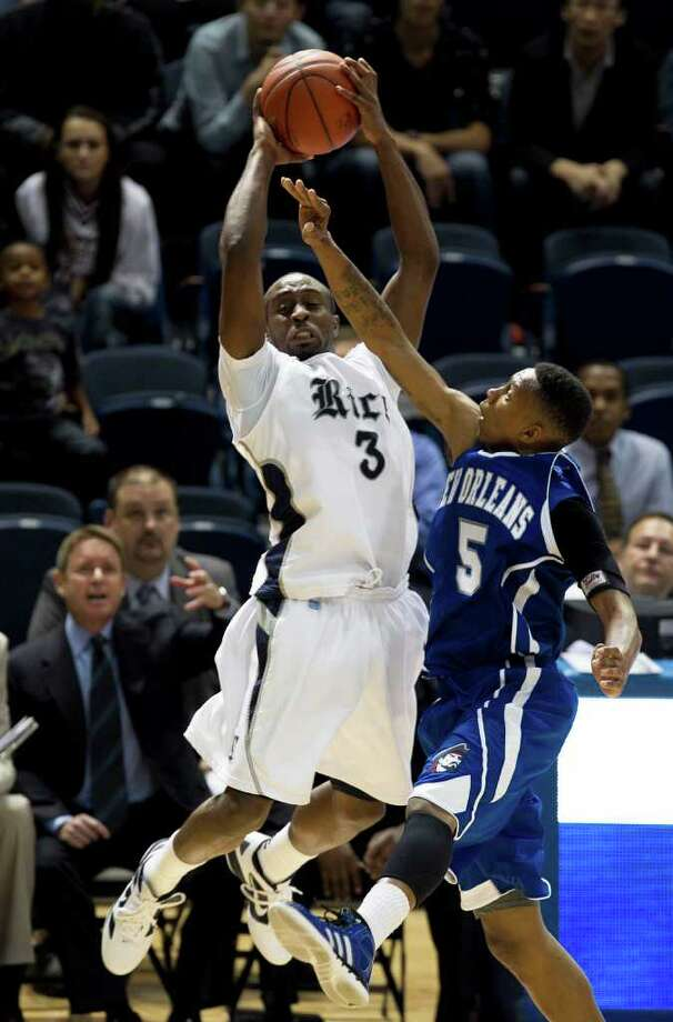 Nov. 12: Rice 83, New Orleans 49. Rice's Tamir Jackson left, passes the ball over New Orleans' Antonio Holmes during the second half. Photo: James Nielsen, Chronicle / © 2011 Houston Chronicle