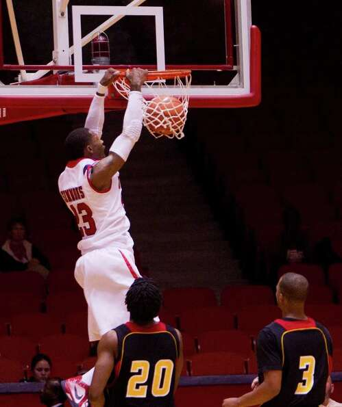 Houston's Jonathon Thomas #23 dunks over Grambling's Roman Higgins #20 and Raschard Boatner #3 durin