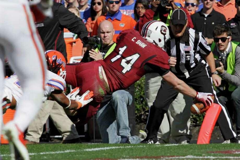 South Carolina quarterback Connor Shaw dives into the end zone past Florida safety Josh Evans. Photo: AP