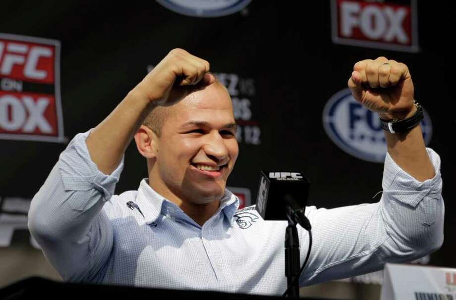 Mixed martial arts fighter Junior Dos Santos raises his arms during a news conference in Los Angeles, Wednesday, Nov. 9, 2011. Dos Santos will fight defending champion Cain Velasquez in a UFC heavyweight title match on Saturday, Nov. 12, in Anaheim, Calif. (AP Photo/Jae C. Hong) Photo: Jae C. Hong / AP