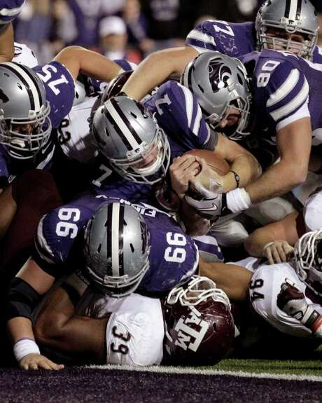 CHARLIE RIEDEL: ASSOCIATED PRESS ABOUT TO GO UNDER: The positioning of Eddie Brown (39) symbolizes Texas A&M's predicament as Kansas State's Collin Klein (7) advances the ball to the 1-yard line in the fourth overtime before ending the game by scoring on the next play. Photo: Charlie Riedel / AP