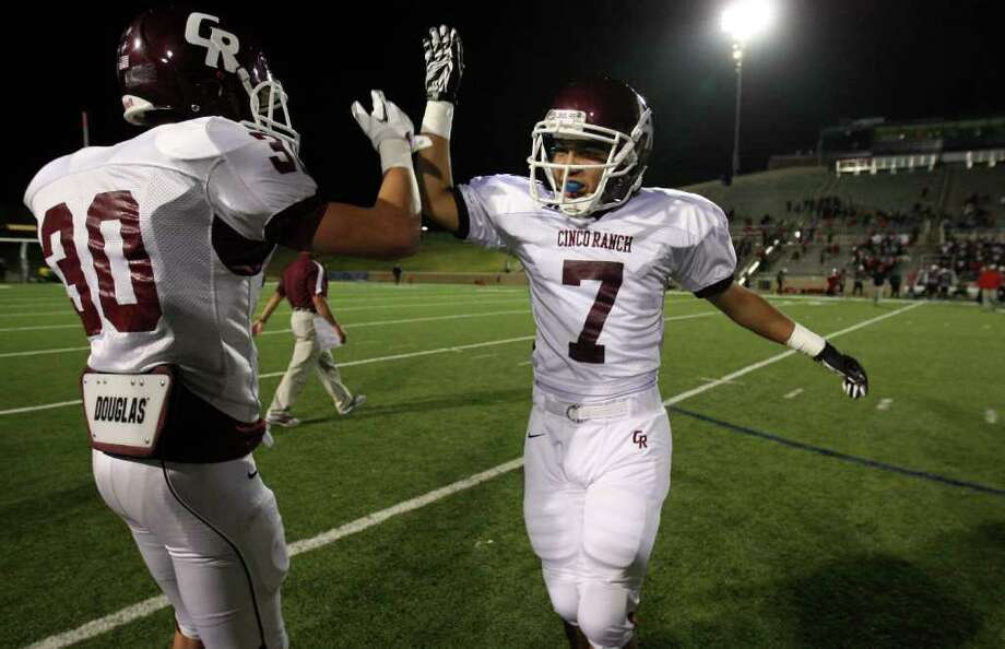 Cinco Ranch's Alex Ramirez (7) celebrates the Cougars' 59-28 victory over the Bellaire Cardinals with teammate Sam Straughan, Saturday, November 1, 2011 at Tully Stadium in Houston. Photo: Eric Christian Smith, For The Chronicle