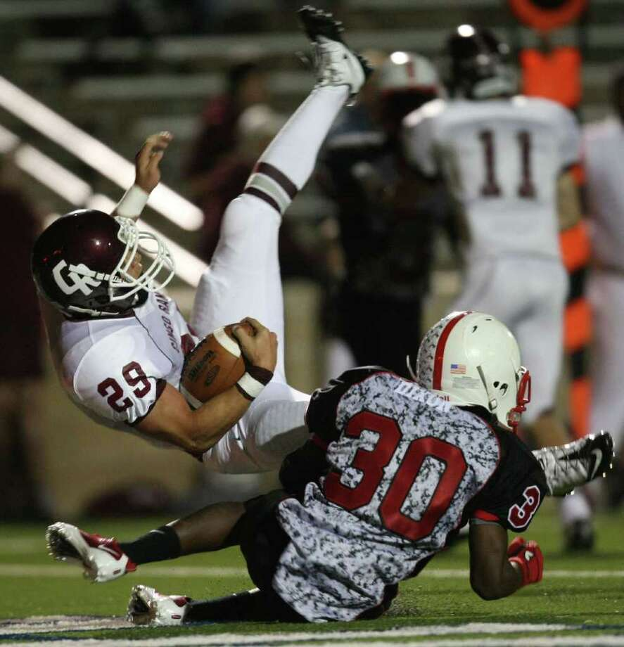 Cinco Ranch's Eyad Elqutub (29) flips over Bellaire's Devante Dixon into the end zone for a touchdown during the second half of a high school football playoff game, Saturday, November 1, 2011 at Tully Stadium in Houston. Photo: Eric Christian Smith, For The Chronicle