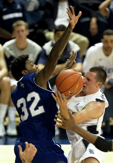 JAMES NIELSEN: CHRONICLE OFF ON THE RIGHT FOOT: Rice's Connor Frizzelle right, collides with the University of New Orleans' Lovell Cook during the host Owls' 83-49 season-opening win Saturday. Photo: James Nielsen / © 2011 Houston Chronicle