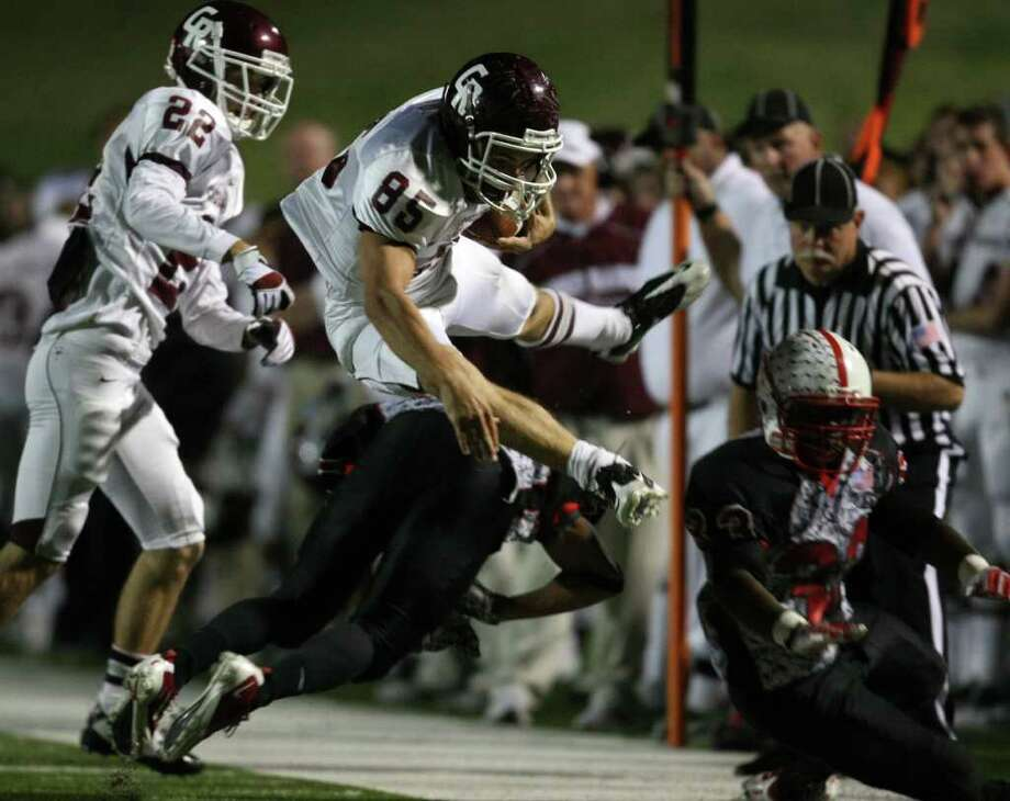 ERIC CHRISTIAN SMITH: FOR THE CHRONICLE HURDLED: Cinco Ranch wide receiver Jake Canfield, center, leaps over Bellaire defender Khari Sharif during the first half Saturday night. Photo: Eric Christian Smith