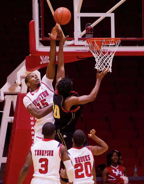 BOB LEVEY: FOR THE CHRONICLE ROMAN CONQUEST: Houston's Leon Gibson goes that extra inch to block a shot by Grambling State's Roman Higgins during Saturday night's game at Hofheinz Pavilion. Photo: Bob Levey / ©2011 Bob Levey
