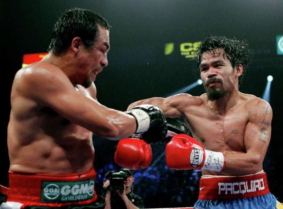 Manny Pacquiao (right) connects on a punch with Mexico's Juan Manuel Marquez during a WBO welterweight title fight Saturday in Las Vegas. Photo: AP