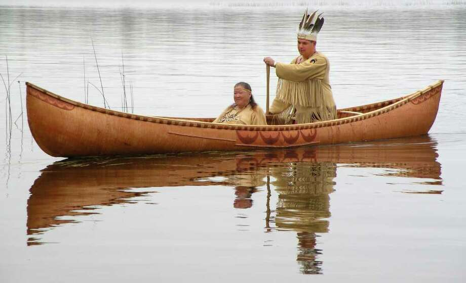 This October 2011 photo provided by the Passamaquoddy tribe shows Chief Joseph Socobasin paddling a birch canoe with his grandmother Joan Dana in Indian Township, Maine. Tribal members built the canoe, a replica of one from the 1800s, using a single piece of birch bark. Though Maine voters rejected a racetrack casino on Nov. 8, 2011, that would have helped bolster the tribe's economy, they are looking to wind, water and land for other means of economic development. (AP Photo/Martin Dana) Photo: Martin Dana