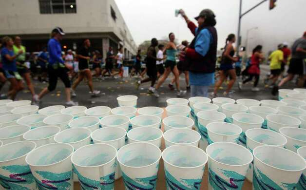 Runners in the Rock 'n' Roll San Antonio Marathon & 1/2 pass a water station near Avenue E and Third Sunday November 13, 2011. Photo: SAN ANTONIO EXPRESS-NEWS