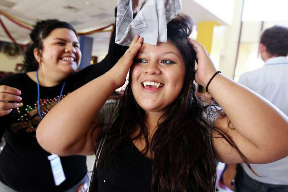 Mentor Gabriela Martinez helps her mentee, Summer Silva, remove the bandana that covered her face after the team made it through an obstacle course. Photo: Jennifer Whitney, Special To The Express-News / special to the Express-News