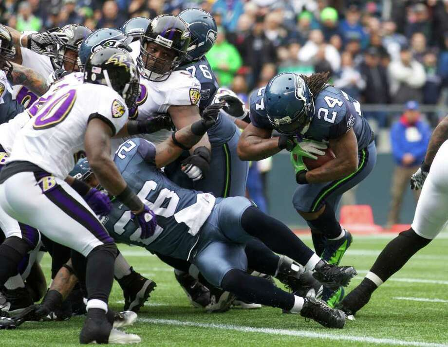 SEATTLE, WA - NOVEMBER 13: Running back Marshawn Lynch #24 of the Seattle Seahawks scores a touchdown against the Baltimore Ravens at CenturyLink Field on November 13, 2011 in Seattle, Washington. Photo: Stephen Brashear, Getty Images / 2011 Getty Images