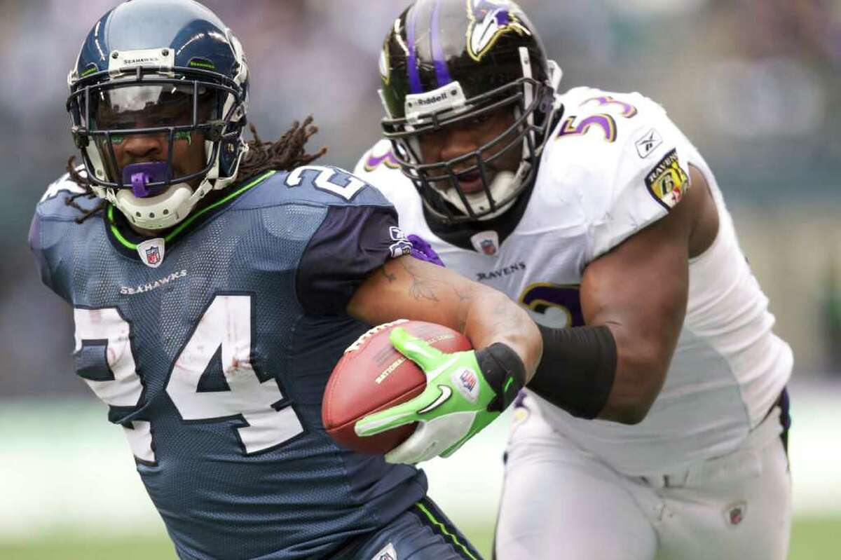 SEATTLE, WA - NOVEMBER 13: Running back Marshawn Lynch #24 of the Seattle Seahawks rushes the ball as linebacker Jameel McClain #53 of the Baltimore Ravens pursues at CenturyLink Field on November 13, 2011 in Seattle, Washington. The run set up a one yard touchdown run for Lynch.