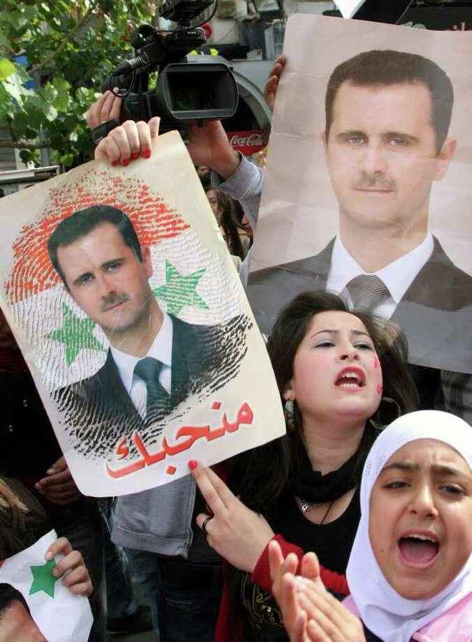 BASSEM TELLAWI: ASSOCIATED PRESS SUPPORTER: Pro-Syrian regime protesters hold portraits of Syrian leader Bashar Assad during a demonstration Sunday. Photo: Bassem Tellawi / AP