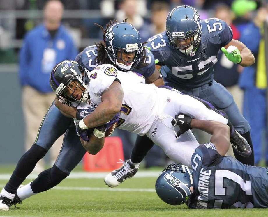 SEATTLE - NOVEMBER 13:  Running back Ray Rice #27 of the Baltimore Ravens is tackled by Richard Sherman #25 and David Hawthorne #57 of the Seattle Seahawks at CenturyLink Field on November 13, 2011 in Seattle, Washington. The Seahawks defeated the Ravens 22-17. Photo: Otto Greule Jr, Getty Images / 2011 Getty Images