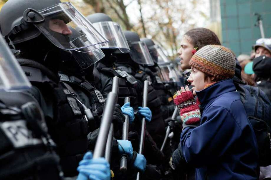 NATALIE BEHRING : GETTY IMAGES FACE TO FACE: A protester pleads with police during a demonstration near Occupy Portland's encampment Sunday. Photo: Natalie Behring / 2011 Getty Images