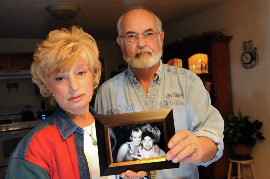 Sheila and Keith Simpson hold a photograph of Jennifer and her brother Jeremy on Friday, Nov. 11, 2011, at their home in Halfmoon, N.Y. Jennifer was found dead in Florida this spring, and her father and step mother are still trying to find answers. (Cindy Schultz / Times Union) Photo: Cindy Schultz / 00015337A