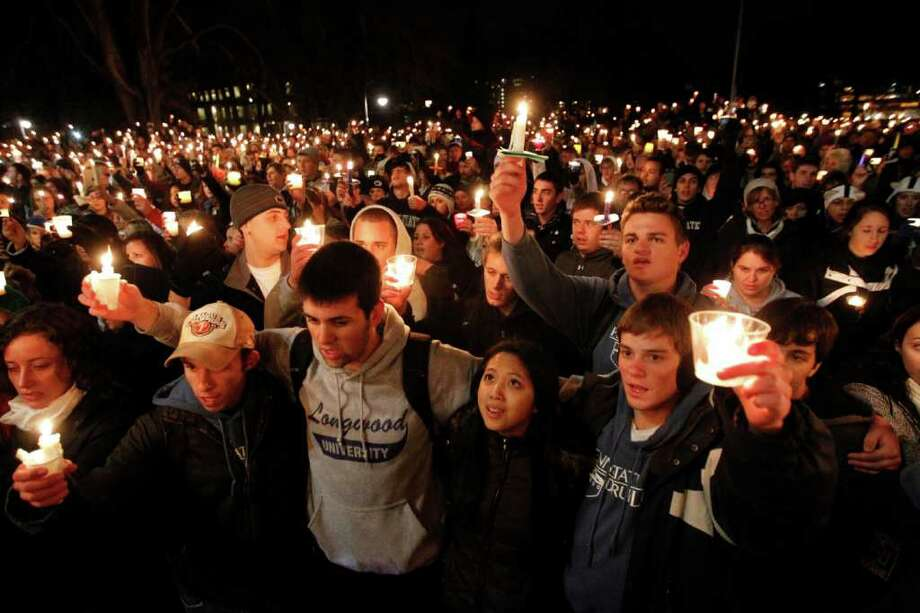 FILE - In this Nov. 11, 2011 file photo, people gather in front of the Old Main building for a candlelight vigil on the Penn State campus in State College, Pa., in support of the alleged victims of a child sex abuse scandal involving a former assistant coach. As Penn State leaves a harrowing week behind and takes tentative steps toward a new normal, students and alumni alike wonder what exactly that means. (AP Photo/Matt Rourke, File) Photo: Matt Rourke