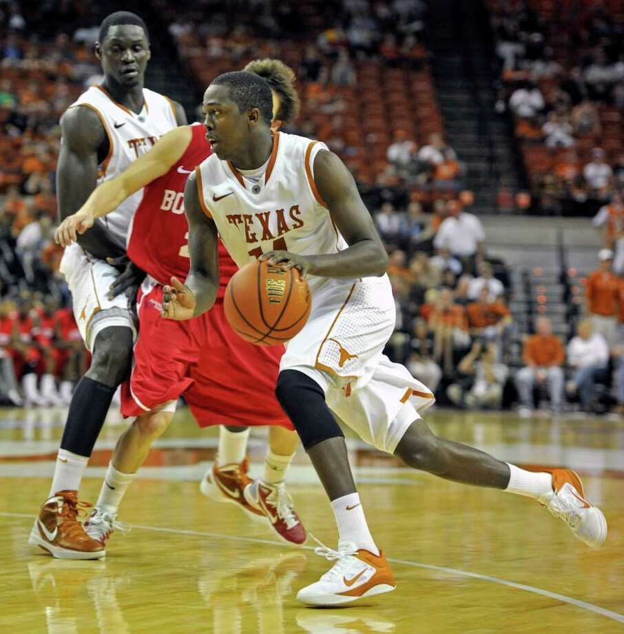 Texas guard J'Covan Brown, front, drives around Boston University guard Matt Griffin, rear, during the second half of the TicketCity Legends Classic NCAA college basketball game Sunday, Nov. 13, 2011, in Austin, Texas. Brown was the leading scorer with 28 points.  Texas won 82-46. (AP Photo/Michael Thomas) Photo: Michael Thomas, Associated Press / FR65778 AP